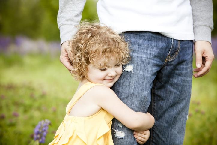 Child hugging father's leg